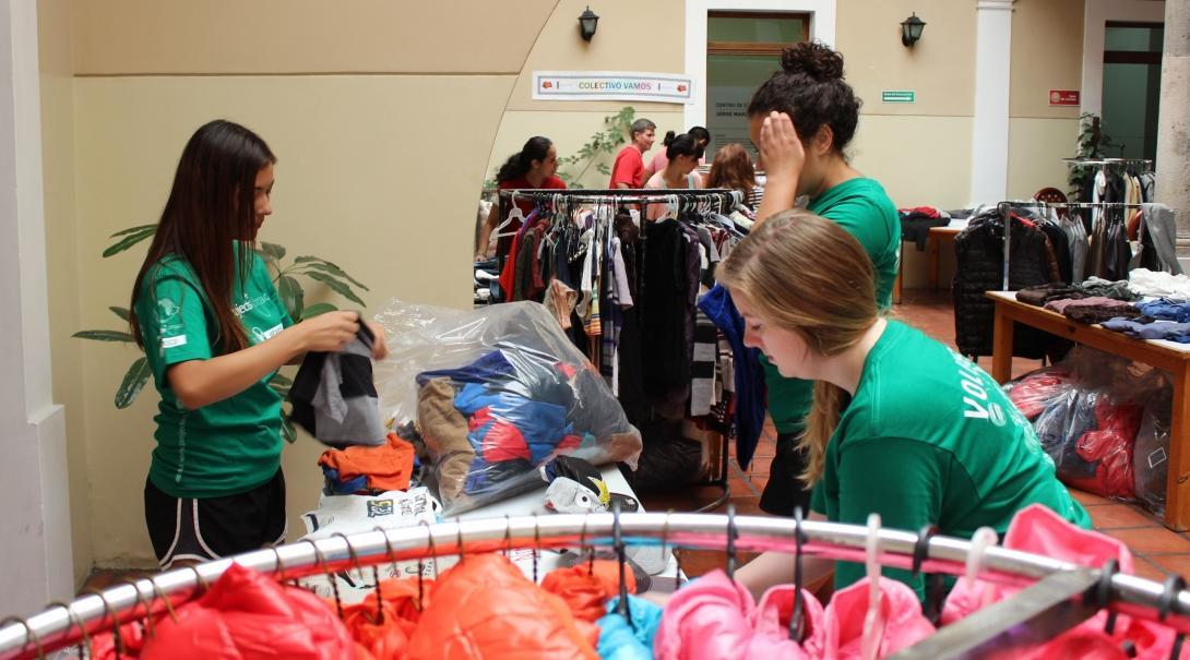Female Interns are sorting through bags of clothes at a clothes companies store during their work placement in Mexico.